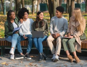 Group of students discussing project, sitting in park
